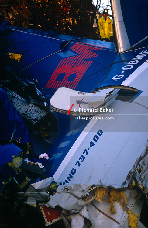 Using ladders and ropes during a rescue operation, Fire Brigade crews enter the floodlit broken air frame of a British Midland Airways Boeing 737-400 series jet airliner which lies on an embankment of the M1 motorway at Kegworth, near East Midlands Airport in Leicestershire, England. On the night of 8th January 1989, flight 92 crashed due to the shutting down of the wrong, malfunctioning engine. Attempting an emergency landing, 47 people died and 74 people, including seven members of the flight crew, sustained serious injuries. The aircraft's tail was snapped upright at ninety degrees. Here perished most of the passenger fatalities. The devastation was hampered by woodland and the fire fighters are attempting to rescue survivors or extract those killed in this air disaster that proved one of Btitain's worst.
