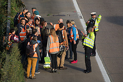 Ockham, UK. 21st September, 2021. Surrey Police officers monitor Insulate Britain climate activists on the hard shoulder beside the clockwise carriageway of the M25 between Junctions 9 and 10. The activists walked into M25 shortly afterwards, blocking both the clockwise and anticlockwise carriageways as part of a campaign intended to push the UK government to make significant legislative change to start lowering emissions.