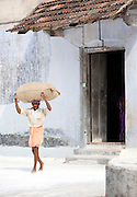 A man carries a bag of spices from a warehouse in Cochin, Kerala, India