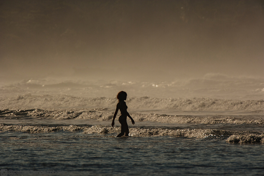 A young mulatto woman wrapped in a purple sarong with curly dark hair is silouhetted as she walks into the surf on the beach in Santa Teresa.