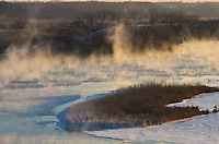Steam rises from the Illinois River as a new day dawns at Starved Rock State Park. The steam is formed due to the near 40 degree difference between the air temperature and the water. The subzero air caused the steam to turn to frost on the small grassy island.<br />