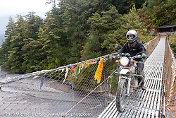 Lowbrow's Mikey Arnold, better known as Mikey Revolt, riding a Royal Enfield Himalayan riding across a suspension bridge in Motorcycle Sherpa's Ride to the Heavens motorcycle adventure in the Himalayas of Nepal. On the fourth day of riding, we went from Kalopani to Muktinath. Thursday, November 7, 2019. Photography ©2019 Michael Lichter.