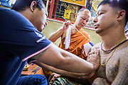 "22 MARCH 2013 - NAKHON CHAI SI, NAKHON PATHOM, THAILAND: A monk gives a man a sacred Sak Yant tattoo at Wat Bang Phra. Wat Bang Phra is the best known ""Sak Yant"" tattoo temple in Thailand. It's located in Nakhon Pathom province, about 40 miles from Bangkok. The tattoos are given with hollow stainless steel needles and are thought to possess magical powers of protection. The tattoos, which are given by Buddhist monks, are popular with soldiers, policeman and gangsters, people who generally live in harm's way. The tattoo must be activated to remain powerful and the annual Wai Khru Ceremony (tattoo festival) at the temple draws thousands of devotees who come to the temple to activate or renew the tattoos. People go into trance like states and then assume the personality of their tattoo, so people with tiger tattoos assume the personality of a tiger, people with monkey tattoos take on the personality of a monkey and so on. In recent years the tattoo festival has become popular with tourists who make the trip to Nakorn Pathom province to see a side of ""exotic"" Thailand. The 2013 tattoo festival was on March 23.    PHOTO BY JACK KURTZ"