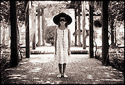 A little girl with a Zorro mask and hat on stands under a breezeway in her backyard.