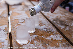 Pouring shots of vodka into shot glasses made of ice at the Baikal Mile Ice Speed Festival. Maksimiha, Siberia, Russia. Thursday, February 27, 2020. Photography ©2020 Michael Lichter.
