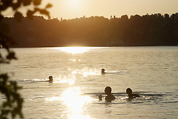 Young adults swimming in lake during sunset, Bavaria, Germany
