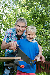 Portrait father son sawing wood building
