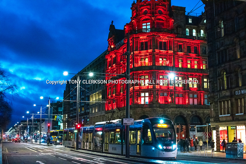 A tram goes through Scotland's capital as dusk falls. NB: As this photo was shot handheld at night, this is a grainy image that will show up on close inspection of any print or product.