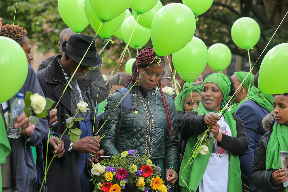 © Licensed to London News Pictures. 14/06/2019. London, UK.  Survivors, family and friends of the victims wearing symbolic green release green balloons to commemorate the second anniversary of the Grenfell Tower fire. On 14 June 2017, just before 1:00am a fire broke out in the kitchen of the fourth floor flat at the 24-storey residential tower block in North Kensington, West London, which took the lives of 72 people. More than 70 others were injured and 223 people escaped. Photo credit: Dinendra Haria/LNP