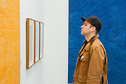 New York, NY - 6 May 2016. Frieze New York art fair. A man looks at a painting by Whanki Kim in Seoul's Hyundai Gallery. Behind him is another painting by Kim.