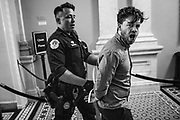 WASHINGTON, USA - July 25: A protestor is escorted out of the Senate Chambers in handcuffs by a Capitol Police Officer after interrupting the vote on the repeal of the Affordable Care Act at the U.S. Capitol in Washington, USA on July 25, 2017.
