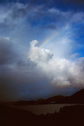 In a Mountain landscape, over a body of water, a dramatic cloud formation is accompanied by a rainbow.