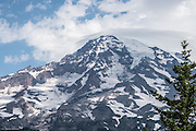 A lenticular cloud blankets the summit of Mt Rainier. The Kautz chut drops from the ice field on the summit and the Kautz Glacier grows from the bowl just beflow the summit.  The Pyramid and Success glaciers are on the left. The Success Cleaver is the large larva wall extending down the left side of the mountain.