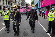 Metropolitan Police and British Transport Police officers attend to animal rights activists from Animal Rebellion who had glued themselves to the top of and inside a truck in order to blockade the Department of Health and Social Care on 3 September 2020 in London, United Kingdom. Animal Rebellion activists are protesting in solidarity with victims of the global food system and to demand that the UK transitions to a sustainable plant-based food system.