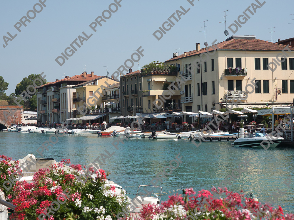 Motorboats parked along the peschiera del garda canal in lake garda, italy during a summer afternoon with clear skies with local businesses in the background