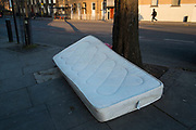 Discarded mattress on a street in Hackney, London, England, UK. This sort of fly tipping is a common sight all over the city as unwanted or rubbish items are thrown away in public. Left for the council to clear up.