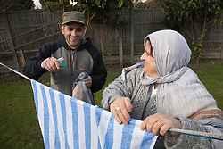 South Asian woman and son hanging up washing on line.