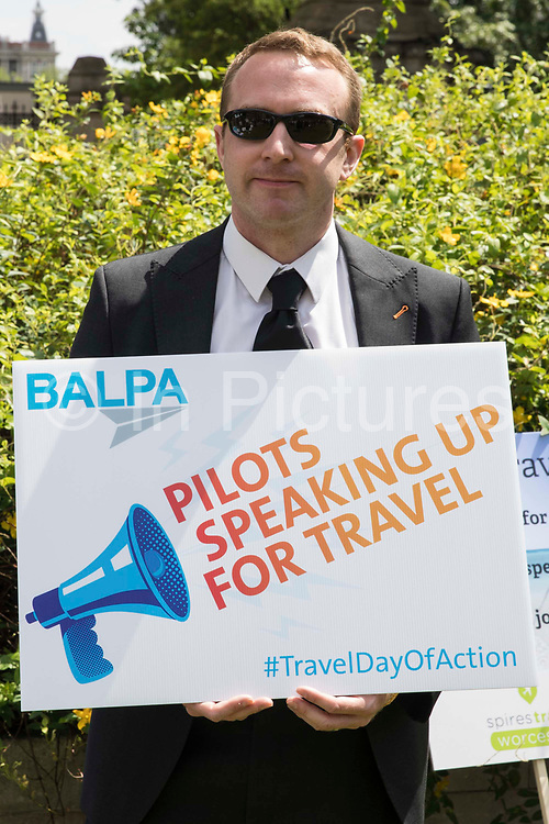 A representative of the British Airline Pilots Association BALPA stands outside the Houses of Parliament during a day of action by the travel industry to apply pressure on the government to reopen the travel sector and to give financial support to travel businesses on 23rd June 2021 in London, United Kingdom. Pilots, cabin crew and travel agents accused the government of failing to restart travel by undermining its Covid-19 traffic light system, which currently does not include viable major tourist destinations on the quarantine-free green list.