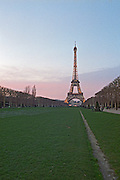 Eiffel Tower illuminated in the evening from Champs de Mars park Paris, France.
