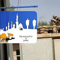 Baghdad, Iraq, 2 Oct 2005. Running 'Route Irish'...Sign outside the camps bar.....B Company, 1st Battalion, The Royal Irish Regiment, a tight-knit multi national fighting force make daily escorting runs along ?Route Irish?, the infamous Baghdad Airport road. The 46 man team are all British Army regulars but come from as far afield as Fiji, South Africa and Northern and Southern Ireland. Previous deployments in Kosovo, Sierra Leone and Northern Ireland have equipped them with the valuable skills needed to provide protection for British Forces and materials transiting the world?s most dangerous highway. Due to an increased presence of US forces along the route both in dug in positions and mobile patrols, attacks along the road have slackened, despite this a day rarely passed without an IED (improvised explosive device) being detonated or a small arms attack against coalition forces. ..The convoy attempts to maintain a seclusion ?bubble? around its vehicles for the duration of the journey. Any civilian vehicle that either strays into the bubble or refuses to keep their distance represents a threat and should they ignore the warning blasts on air horns carried in each vehicle the rules of engagement progress from warning shots to use of lethal force. The relative safety of the International Zone offers them an opportunity to decompress between missions. A duty driver ferries soldiers to the ?Liberty Pool?. Once only frequented by Iraq?s Ba?athist elite the luxury swimming pool and gym now fills with troops. Their body armour, helmets and weapons all within easy reach they either soak up the sun or compete with each other in diving competitions. After a daily briefing the troops have access to the ?Mosquito and Camel? bar where they watch TV or play pool and in accordance with the ?2 can rule? are allowed to drink 2 beers per night.