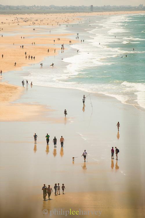 People walking on Conil de la Frontera beach in Andalucia, Spain