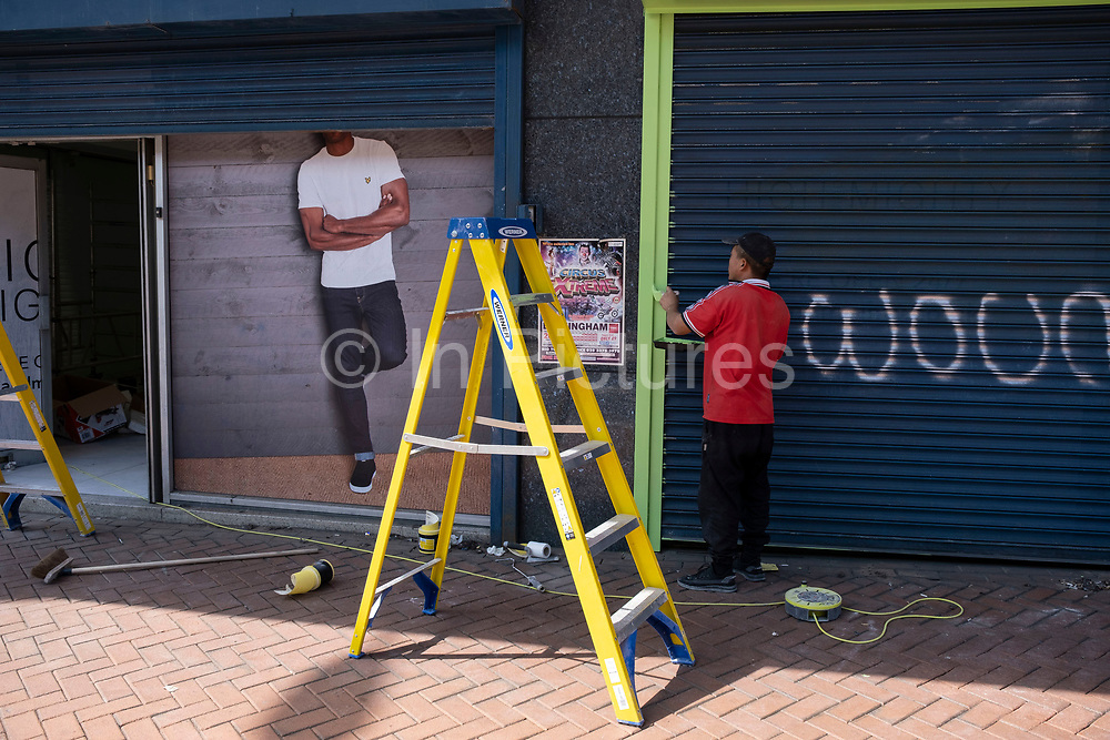 Man beside a ladder painting the exterior of a shop interacts with a printed picture of a model whose head is obscured by shutters on 14th July 2021 in Birmingham, United Kingdom. The figures are in scale with one another despite being real in 3D or two dimensional.