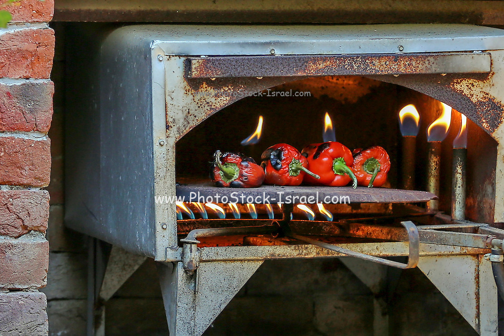 Red bell peppers in an open flame gas oven