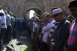 July 19, 2017 - 19.07.17 Lion's Gate, Jerusalem- Muslim's hold afternoon prayer outside Lion's Gate as Israeli Police look on. Clashes between Muslim protesters and police outside Lion's Gate in Jerusalem's Old City. (Credit Image: © Louise Wateridge via ZUMA Wire)