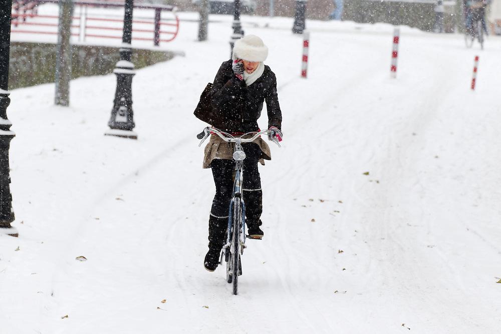 Druk bellend fietst een vrouw in de sneeuw over de Van Asch van Wijckkade in Utrecht.<br /> <br /> A woman is cycling in the snow at the Van Asch van Wijckkade Utrecht while she is on the phone.
