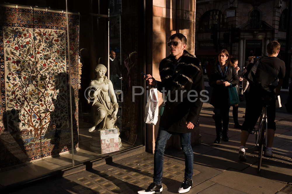 A fashion conscious male with a small girl statue credited to the 19th century Florence-born artist Raffaello Romanelli. In afternoon sunlight, the young man walks near the corner of Albermarle Street and Piccadilly, London W1, Westminster. His sense of style and confidence shows in the way he strides along the street surrounded by other Londoners whereas the classical statuette looks on, admiring the passers-by, her bare breast and wearing the stylish jewellery of the era.