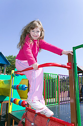 Little girl playing on a climbing frame in the playground,