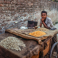 A youngster vends his nuts and snacks along a road  in Dhaka, Bangladesh.