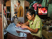 10 SEPTEMBER 2015 - BANGKOK, THAILAND:  A woman does seamstress work in her home  on Thetsaban Sai 1 Road, a pedestrian footpath next to Wat Kalayanamit. The woman's home, and other homes on the path, are scheduled to be demolished in the next week. Authorities started to destroy 54 homes in front of Wat Kalayanamit, a historic Buddhist temple on the Chao Phraya River in the Thonburi section of Bangkok. Government officials, protected by police, seized the house of Chaiyasit Kittiwanitchapant, a Kanlayanamit community leader, who has led protests against the temple's abbot for trying to evict community members whose houses are located around the temple. Work crews went into Chaiyasit's home and took it apart piece by piece. The abbot of the temple said he was evicting the residents, who have lived on the temple grounds for generations, because their homes are unsafe and because he wants to improve the temple grounds. The evictions are a part of a Bangkok trend, especially along the Chao Phraya River and BTS light rail lines, of low income people being evicted from their long time homes to make way for urban renewal.    PHOTO BY JACK KURTZ