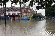 A wide landscape of flooding in an inner-city road junction. A burst water main closed the otherwise busy junction of Half Moon Lane and Dulwich Road in the south London area of Herne Hill. At about 5am, emergency crews were called when water inundated local homes and businesses, forcing residents to evacuate their properties and leave before electricity supplies were shut down.