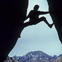 ROCK CLIMBING. Climber bouldering in Buttermilk Rocks, CA. (Sierra Nevada) Basin Mountain bkg.