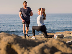 Man and woman stretching on the beach of Azkorri