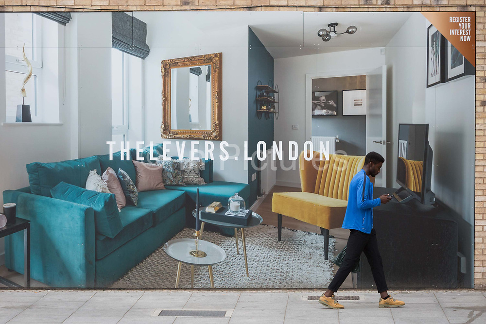 A Londoner walks past a marketing billboard for The Levers - a new apartment development on the Walworth Road at Elephant And castle, on 4th September 2018, in Southwark, London, England. The Levers A Peabody development will be a complex of 1,2,and 3 bed flats close to Elephant & Castle and Elephant Park - both undergoing major redevelopment.