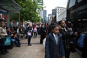 School children and workers at a bus stop in central Birmingham, United Kingdom.