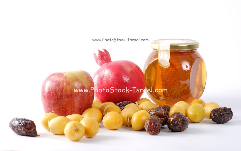 Apples, Honey, pomegranate, and dates, Symbols of Roah Hashanah the Jewish New Year on white background.