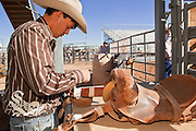 26 NOVEMBER 2011 - CHANDLER, AZ:    CHANCE BARNES repairs his saddle before the saddle bronc riding at the Grand Canyon Pro Rodeo Association (GCPRA) Finals at Rawhide Western Town in west Chandler, AZ, about 20 miles from Phoenix Saturday. The GCPRA Finals is the last rodeo of the GCPRA season. The GCPRA is a professional rodeo association based in Arizona.  PHOTO BY JACK KURTZ