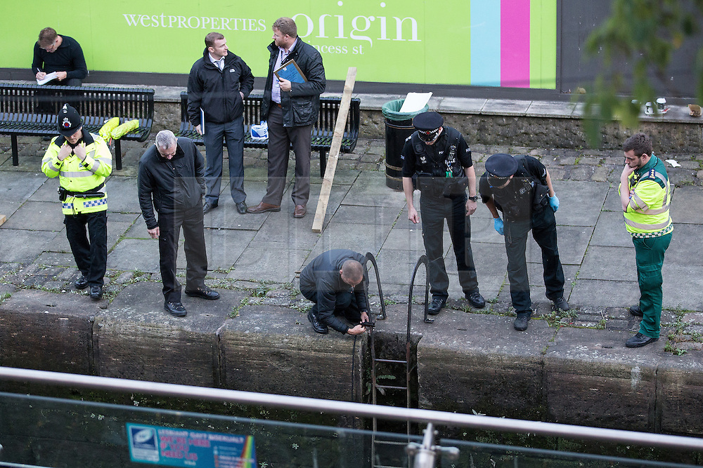 """© Licensed to London News Pictures . Manchester , UK . FILE PICTURE DATED  06/10/2013 of police examining a body floating in a canal , prior to recovering it . Police pulled a body from The Bridgewater Canal in Manchester , adjacent to the City's """" Gay Village """" on Canal Street . Greater Manchester Police have issued a statement after suggestions that a number of deaths in and around Manchester's canals may be linked to a serial killer , named in local folklore as """" The Pusher """" . The statement said """" Absolutely no evidence whatsoever of foul play has been established """" . Photo credit : Joel Goodman/LNP"""