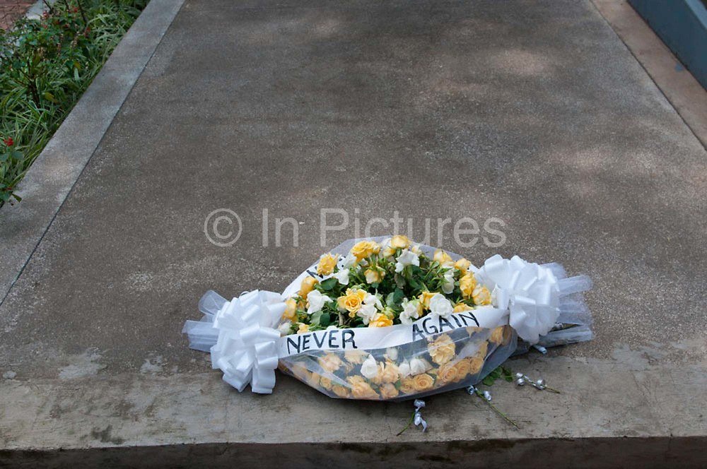 Rwanda February 2014. Kigali Genocide Memorial.  A wreath of flowers with the words 'Never Again' lies on one of the mass graves. 250,000 people are buried here, victims of 1994 genocide when an estimated 800,000 to one million people were savagely killed in 100 days ,starting on April 7th when the President's plane was shot down.