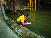 """26 NOVEMBER 2014 - BANGKOK, THAILAND: A performer washes his hands in the Chao Phraya River before a Chinese opera performance at the Chow Su Kong Shrine in the Talat Noi neighborhood of Bangkok. Chinese opera was once very popular in Thailand, where it is called """"Ngiew."""" It is usually performed in the Teochew language. Millions of Chinese emigrated to Thailand (then Siam) in the 18th and 19th centuries and brought their culture with them. Recently the popularity of ngiew has faded as people turn to performances of opera on DVD or movies. There are about 30 Chinese opera troupes left in Bangkok and its environs. They are especially busy during Chinese New Year and Chinese holidays when they travel from Chinese temple to Chinese temple performing on stages they put up in streets near the temple, sometimes sleeping on hammocks they sling under their stage.      PHOTO BY JACK KURTZ"""