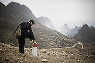 An ethnic man stops at a kilometre marker to fix his sandal. Ha Giang province, Vietnam, Asia