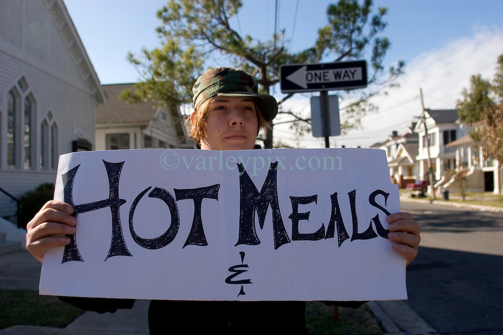 21 December 05. New Orleans, Louisiana. Post Katrina aftermath.<br />  Volunteer Chris Johnston (17 yrs) holds up a sign for free Hot meals, dished out by a volunteer church group who traveled from Pittsburg to help residents in Mid City.<br /> Photo; ©Charlie Varley/varleypix.com
