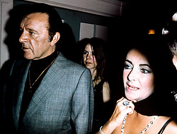 Richard Burton and his wife Elizabeth Taylor at Burton's 50th birthday party at the Dorchester Hotel, London