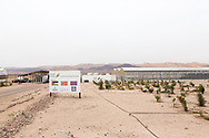 An overview of The Sahara Forest Project on the outskirts of Aqaba, on Jordan's southern Red Sea coastline. A couple of hundred meters behind the farm, seen at the rear of the image, is the Israeli border with Jordan. The farm uses desalinated sea water and greenhouses to sustainably farm crops in land that was once aris desert.