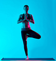 one caucasian woman exercising tree pose Vriksasana yoga exercices  in silhouette studio isolated on blue background