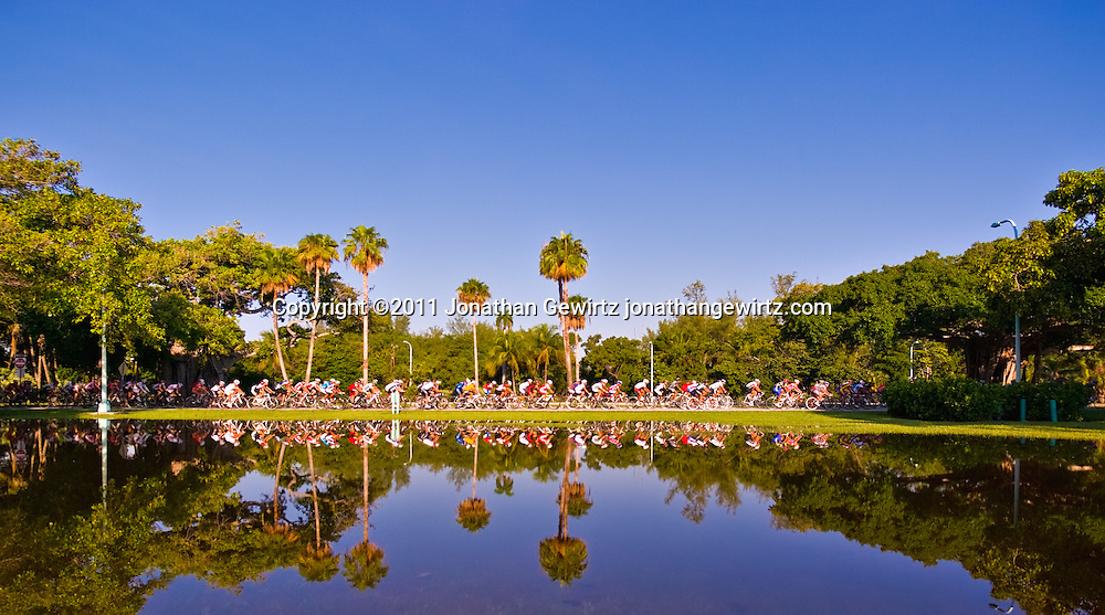 A large pack or peleton of cyclists is reflected in a pool of rainwater at Crandon Park, Key Biscayne, Florida. WATERMARKS WILL NOT APPEAR ON PRINTS OR LICENSED IMAGES.
