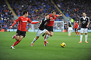 Southampton's Adam Lallana(c) battles with Cardiff City's Ben Turner during the Barclays Premier league, Cardiff city v Southampton at the Cardiff city Stadium in Cardiff,  South Wales on Boxing day, Thursday 26th Dec 2013. <br /> pic by Jeff Thomas, Andrew Orchard sports photography.